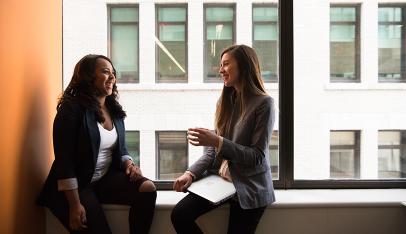 two women talk in office space